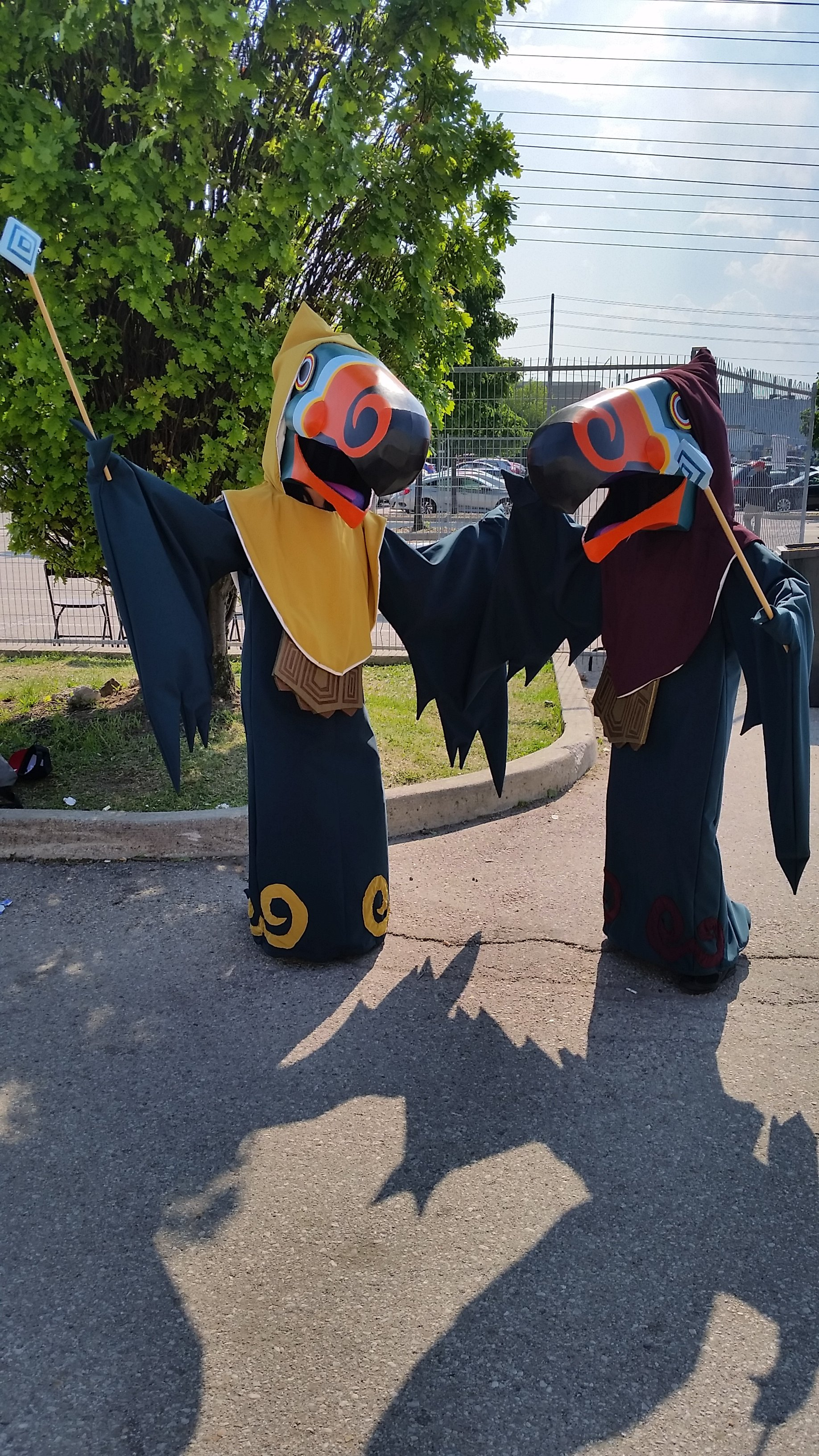 Two cosplays of the Wizzrobe enemies from The Legend of Zelda Wind Waker. They each have different hood colours - one in yellow and the other in maroon.