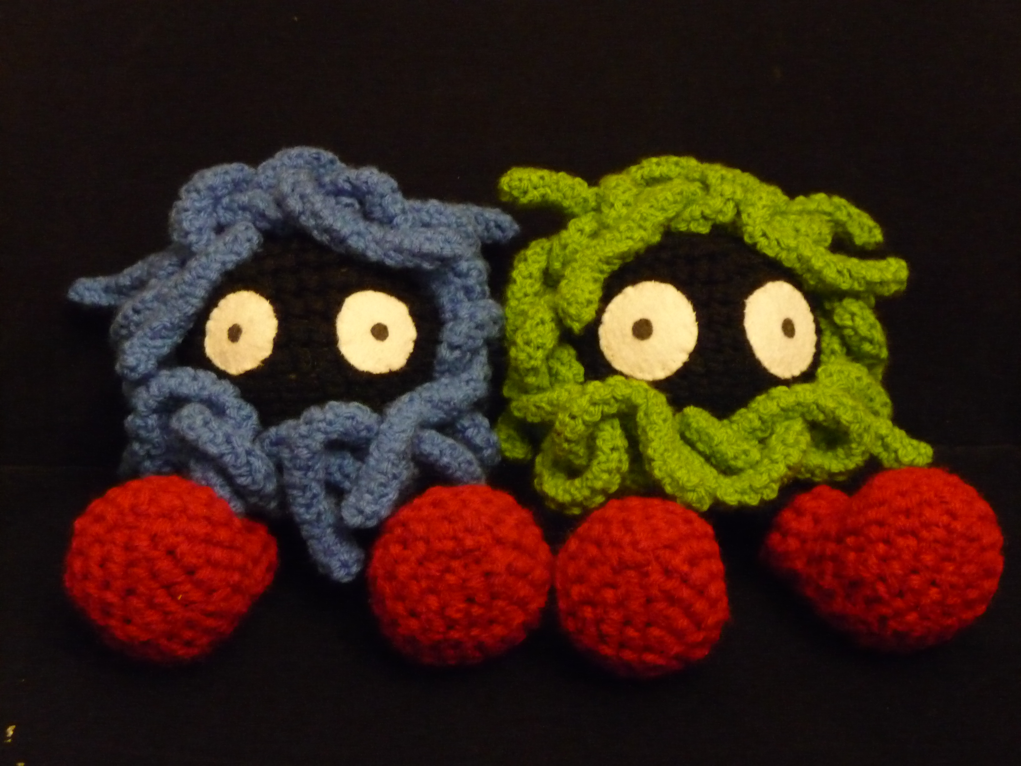 two crocheted versions of the pokemon Tangela, one in blue and the other in green. This is the front view.