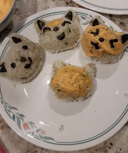 Cat shaped rice balls, topped with spicy mayonnaise and seaweed shapes