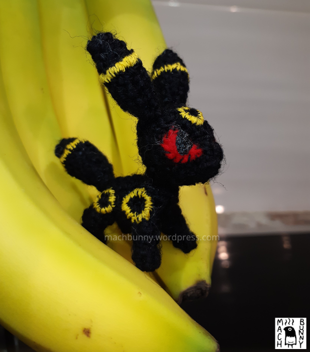 Tiny amigurumi Umbreon, front view on a banana
