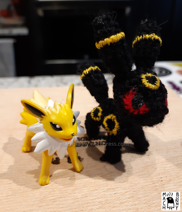 Tiny amigurumi Umbreon, front view comparison with a jolteon figurine