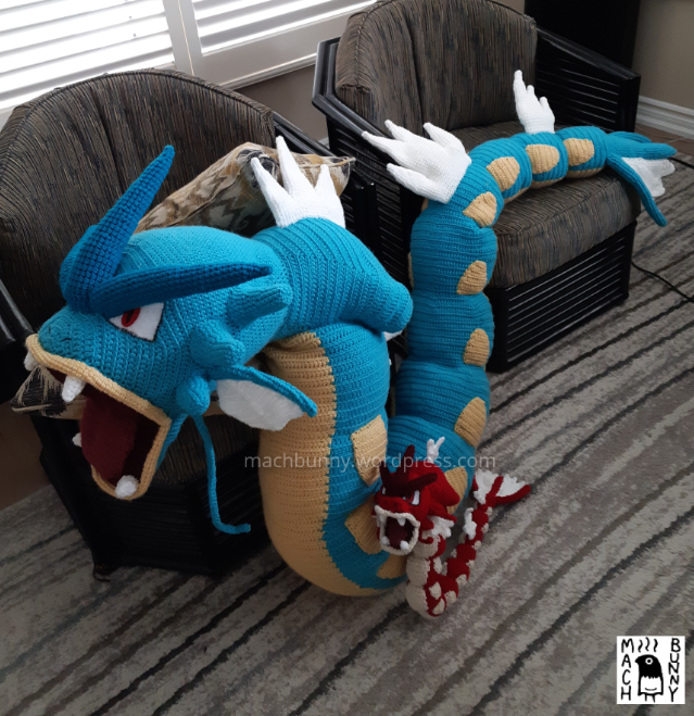 Giant amigurumi Gyarados, front view in comparison to tiny shiny amigurumi gyarados