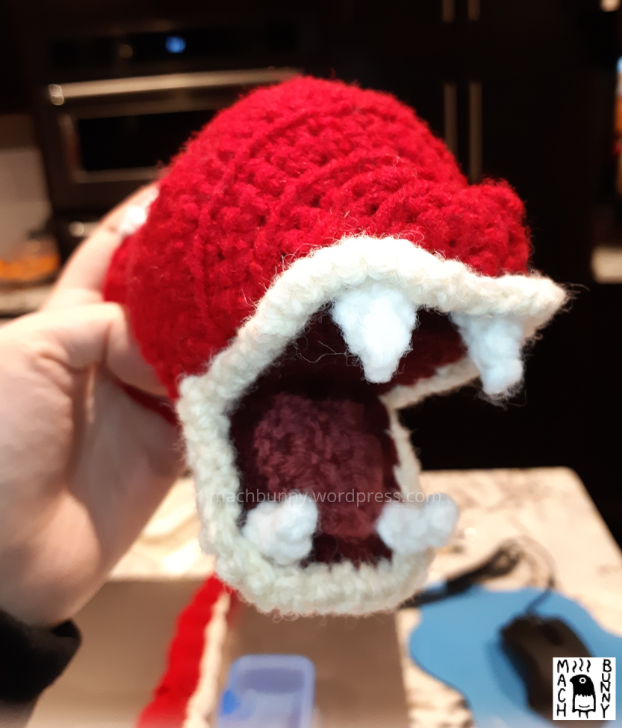 Tiny shiny amigurumi Gyarados, front view of the face with lips and tongue and teeth