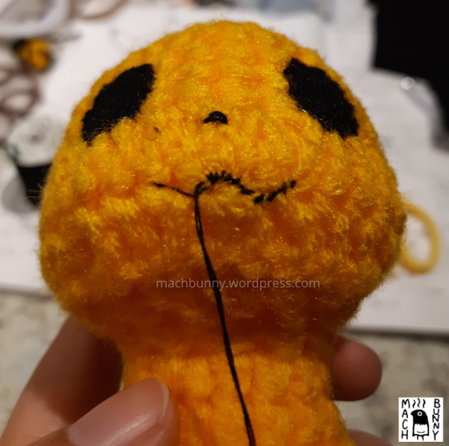 Amigurumi Detective Pikachu, front view of face with eyes, mouth, and nose stitched in place