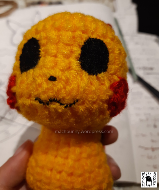 Amigurumi Detective Pikachu, front view of face with eyes, mouth, cheeks, and nose stitched in place
