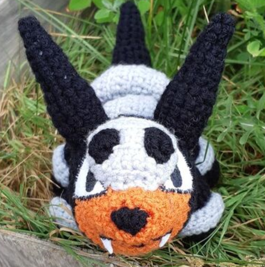 Houndour amigurumi, front view of face in grass