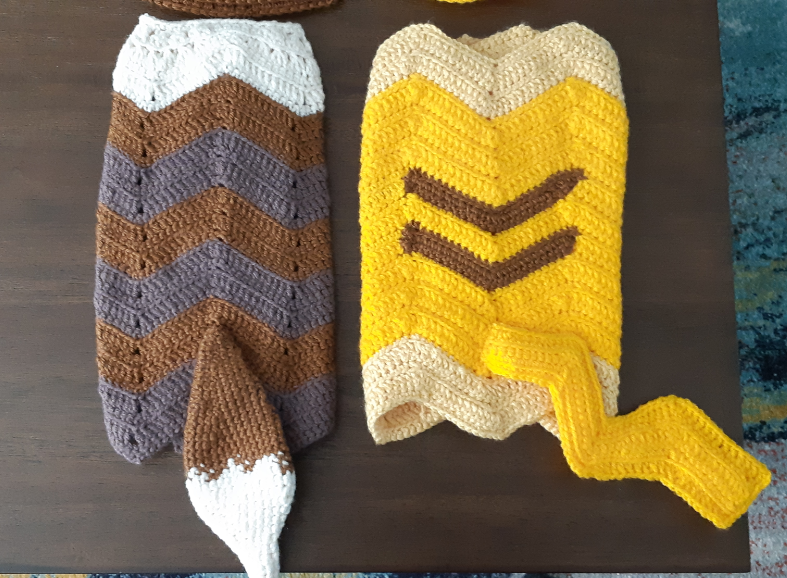 Completed blanket sets of the eevee and pikachu. Pikachu blanket features two brown stripes on a yellow and cream zig zag blanket and a zig zag tail. Eevee blanket features a brown and grey-brown striped zig zag blanket with off-white on one side and the tail on the opposite end.