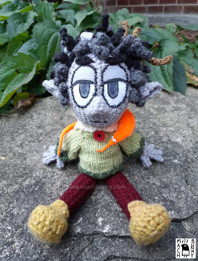 A crocheted Dungeons and Dragons character, named Borgo. The character is a rock gnome, resembling a human-like person with grey skin and pointed ears. Hair is a combination of black and white and is somewhat messy with two twigs sticking out. Character is wearing a green sweater with an off-white collar and red button, maroon pants, and a mustard shade of shoes. Around the neck is a bright orange worm-on-a-string.