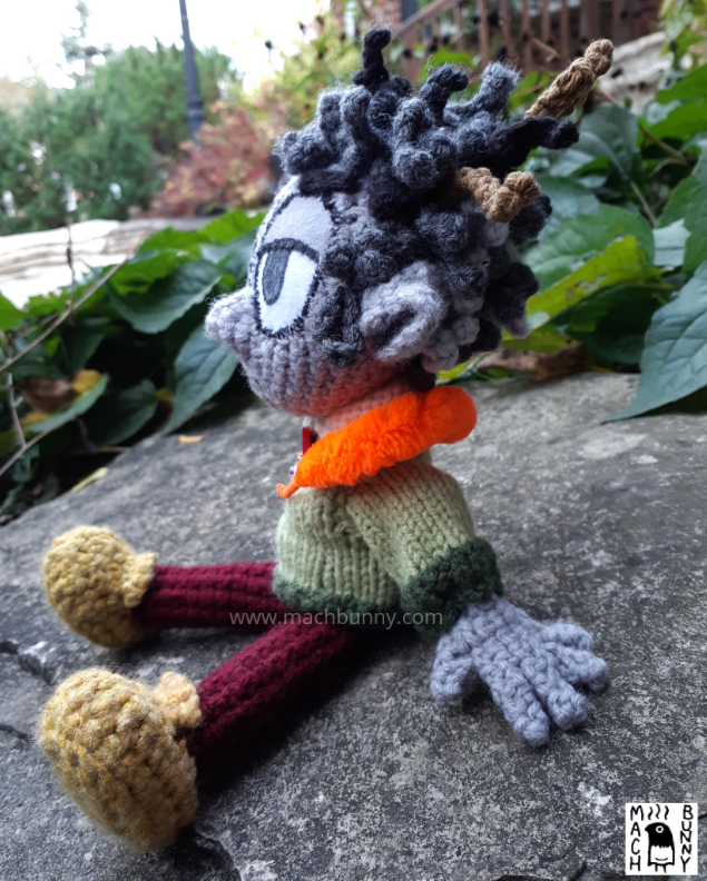 A crocheted Dungeons and Dragons character, named Borgo. The character is a rock gnome, resembling a human-like person with grey skin and pointed ears. Hair is a combination of black and white and is somewhat messy with two twigs sticking out. Character is wearing a green sweater with an off-white collar and red button, maroon pants, and a mustard shade of shoes. Around the neck is a bright orange worm-on-a-string. The angle is looking from the left side.
