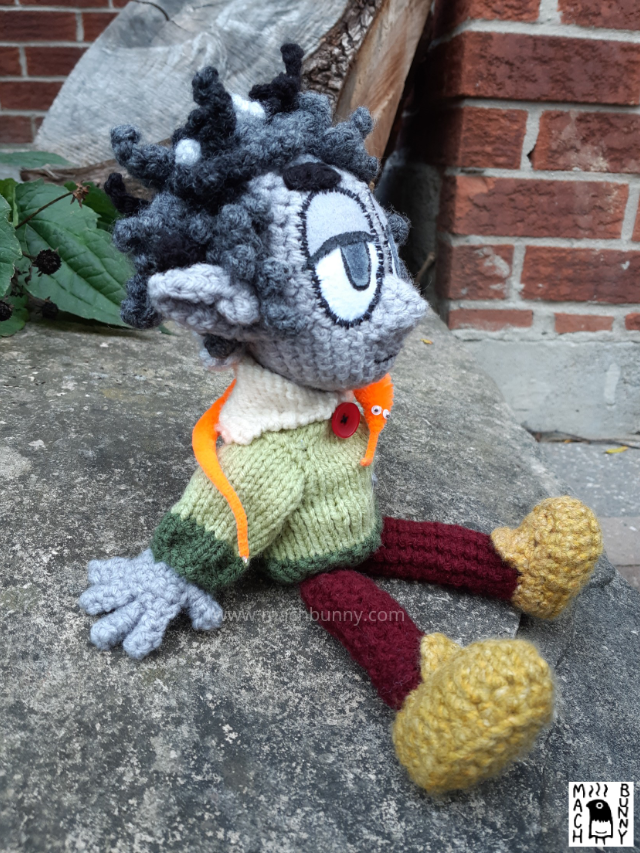 A crocheted Dungeons and Dragons character, named Borgo. The character is a rock gnome, resembling a human-like person with grey skin and pointed ears. Hair is a combination of black and white and is somewhat messy with two twigs sticking out. Character is wearing a green sweater with an off-white collar and red button, maroon pants, and a mustard shade of shoes. Around the neck is a bright orange worm-on-a-string. The angle is looking from the right side.