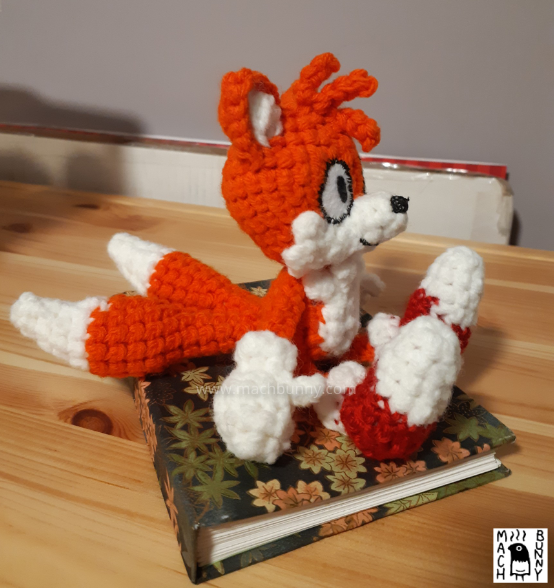 Image of a crocheted fox, named Tails. The character is an orange fox with three orange hairs in the front, white inner ears, muzzle, and tail tips. The character is also wearing white gloves and red shoes with white tips. The crocheted doll is sitting on a notebook. It is a side profile looking towards the right.