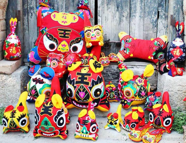 An image of several Chinese cloth tiger toys. The designs are brightly coloured with bold markings and floral motifs.