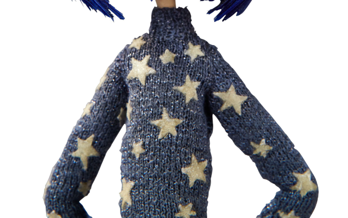 A clip of Coraline's blue sweater with stars; picture is cropped to focus on the small details of the hand-knitted sweater.