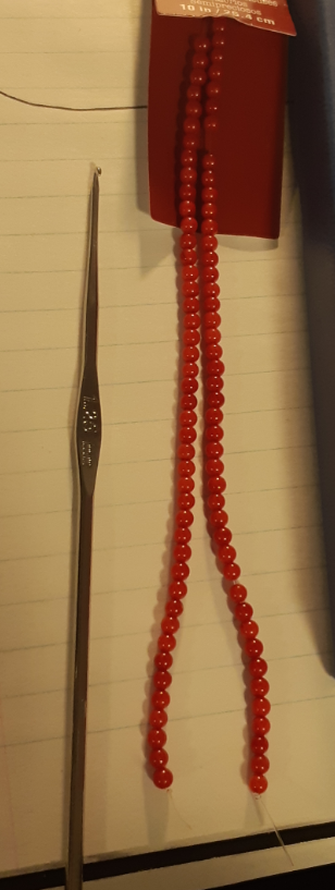 A picture of the string of beads, next to the crochet hook for scale. Beads are 3mm in size and are red in colour.